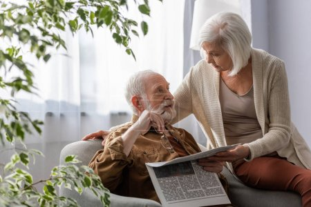 Photo for Senior woman talking to husband holding newspaper and eyeglasses while sitting in armchair - Royalty Free Image