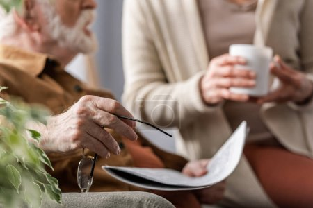 cropped view of senior man holding eyeglasses and newspaper near wife with cup of tea, selective focus