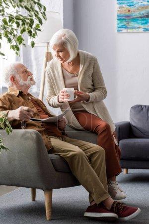 Photo pour Senior femme tenant tasse de thé tout en parlant à mari assis dans le fauteuil avec journal - image libre de droit