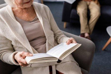 Photo pour Vue recadrée du livre de lecture de femme âgée près du mari, foyer sélectif - image libre de droit