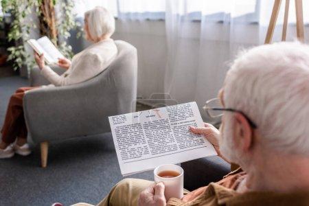 Selektiver Fokus eines älteren Mannes, der eine Tasse Tee in der Hand hält und Zeitung liest, während seine Frau im Sessel Buch liest