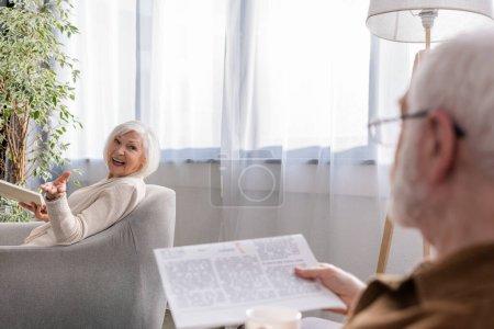 Photo pour Femme heureuse assise dans un fauteuil avec un livre tout en parlant au mari avec un journal - image libre de droit