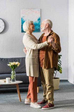 Photo pour Heureux couple de personnes âgées dansant tout en se regardant près de la table avec des tulipes - image libre de droit