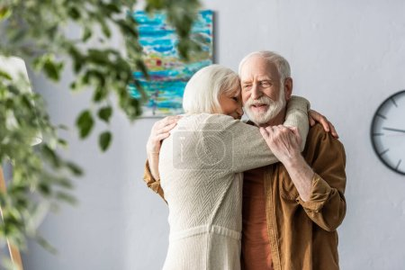 selective focus of happy senior man hugging smiling wife