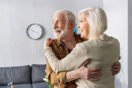 Photo pour Joyeux couple de personnes âgées dansant, riant et regardant loin à la maison - image libre de droit
