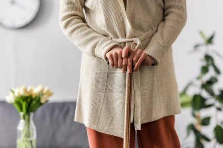 cropped view of senior woman standing with walking stick at home