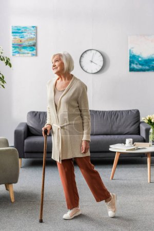 happy senior woman looking away while standing with walking stick at home