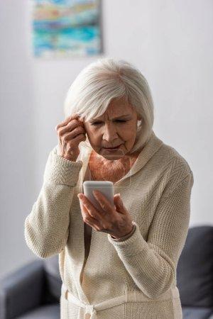 Photo pour Femme âgée réfléchie toucher la tête tout en utilisant un smartphone à la maison - image libre de droit
