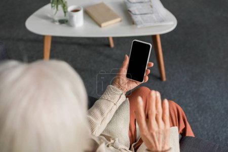 Photo for Overhead view of senior woman holding smartphone with blank screen while sitting near table - Royalty Free Image