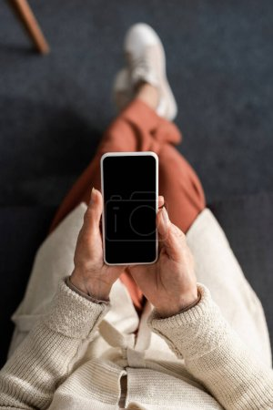 top view of senior woman holding smartphone with blank screen