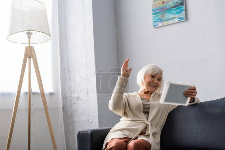 excited senior woman sitting with raised hand while using digital tablet