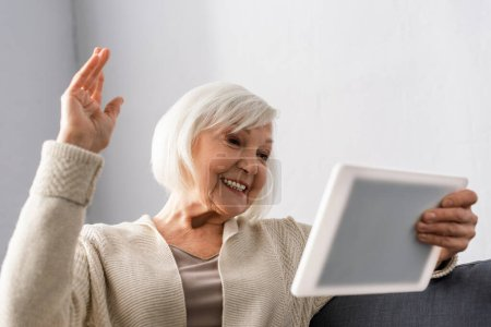 Photo for Cheerful senior woman sitting with raised hand while using digital tablet - Royalty Free Image