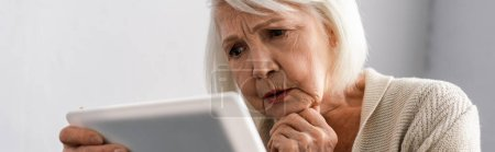 horizontal image of thoughtful senior woman holding hand near chin while using digital tablet