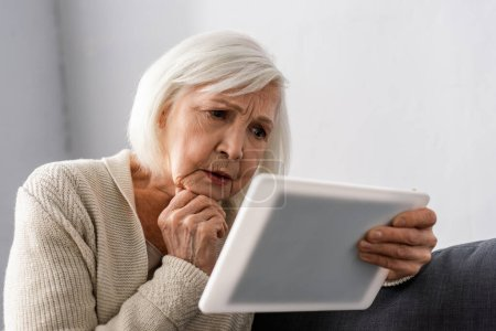 Photo for Worried senior woman holding hand near chin while using digital tablet - Royalty Free Image