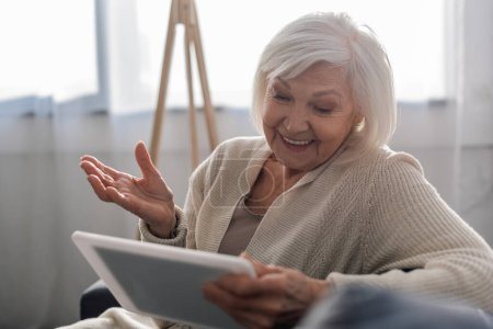 selective focus of cheerful senior woman sitting with open arm while using digital tablet
