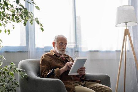 Photo pour Homme âgé concentré utilisant une tablette numérique tout en étant assis dans le fauteuil - image libre de droit