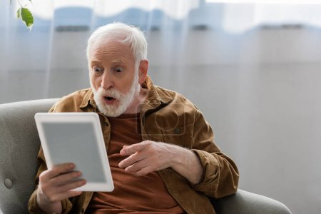 shocked senior man pointing with finger while using digital tablet
