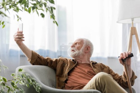 Photo for Selective focus of senior man sitting in armchair and taking selfie on smartphone - Royalty Free Image