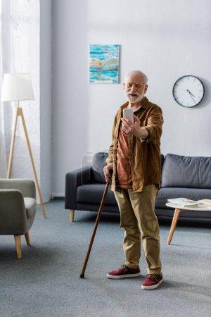 Photo pour Heureux homme âgé debout avec bâton de marche et de prendre selfie sur smartphone - image libre de droit