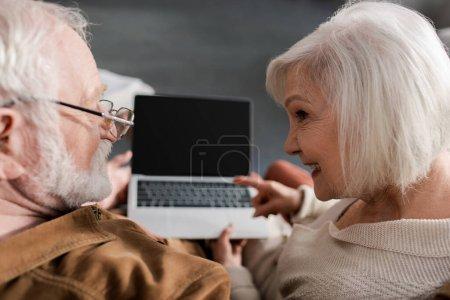 Photo pour Vue aérienne de la femme âgée souriante pointant vers un ordinateur portable avec écran blanc tout en étant assis près du mari, mise au point sélective - image libre de droit