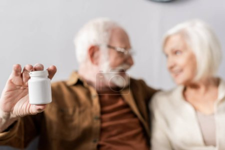 selective focus of cheerful senior man showing pills container while looking at smiling wife