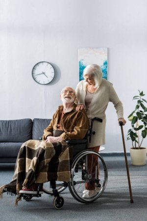 Photo for Senior woman with walking stick and handicapped man in wheelchair smiling while looking at each other - Royalty Free Image