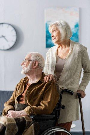 Photo pour Femme âgée avec bâton de marche touchant l'épaule du mari handicapé assis en fauteuil roulant - image libre de droit