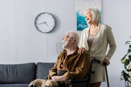 Photo for Senior woman and handicapped husband in wheelchair laughing while looking away - Royalty Free Image
