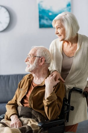 Photo for Smiling senior woman and cheerful disabled husband holding hands and looking away - Royalty Free Image