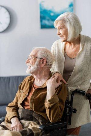 Photo pour Femme âgée souriante et mari handicapé joyeux tenant la main et détournant les yeux - image libre de droit