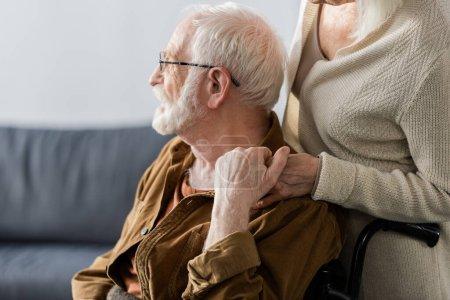 Photo pour Vue recadrée de la femme âgée touchant la main du mari handicapé - image libre de droit
