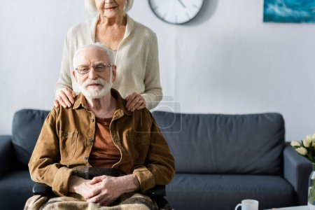 Photo for Cropped view of senior woman touching shoulders of disabled husband sitting in wheelchair - Royalty Free Image