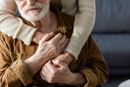 Photo pour Vue recadrée de la femme embrassant mari aîné et tenant ses mains - image libre de droit