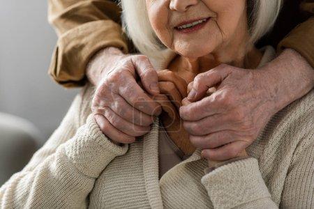 Photo pour Vue partielle d'un homme âgé tenant la main d'une femme souriante - image libre de droit
