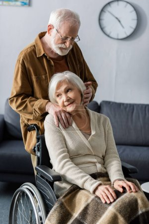 Photo for Smiling, dreamy senior woman sitting in wheelchair while husband holding hand on her shoulder and touching hair - Royalty Free Image