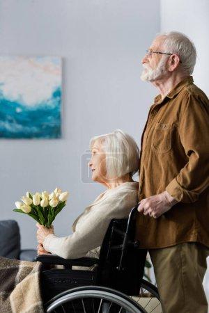 Photo pour Vue latérale de l'homme âgé debout derrière femme handicapée assis en fauteuil roulant avec bouquet de tulipes - image libre de droit
