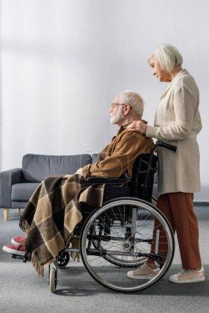Photo pour Vue latérale de la femme âgée touchant l'épaule du mari handicapé, malade de démence - image libre de droit