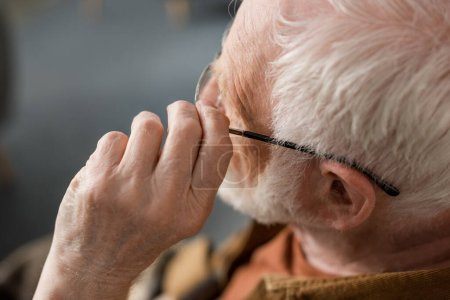 overhead view of alone senior man touching eyeglasses