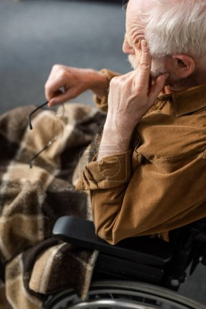 Photo for Disabled senior man touching face and holding eyeglasses while sitting in wheelchair - Royalty Free Image