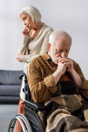 Photo pour Foyer sélectif de triste femme âgée debout derrière handicapé, malade assis en fauteuil roulant avec les mains pliées - image libre de droit