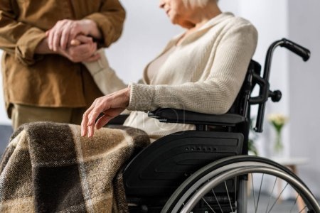 cropped view of senior man holding hand of handicapped, ill wife in wheelchair