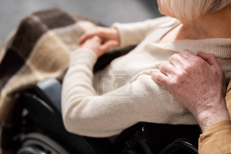 cropped view of man touching shoulder of handicapped, diseased wife sitting in wheelchair