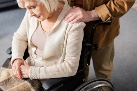 cropped view of senior man touching shoulder of disabled wife sitting in wheelchair with bowed head