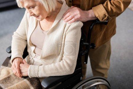 vue recadrée d'un homme âgé touchant l'épaule d'une femme handicapée assise en fauteuil roulant avec la tête inclinée