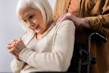 Photo pour Vue recadrée du mari touchant les épaules de la femme âgée pleurant alors qu'elle était assise en fauteuil roulant - image libre de droit