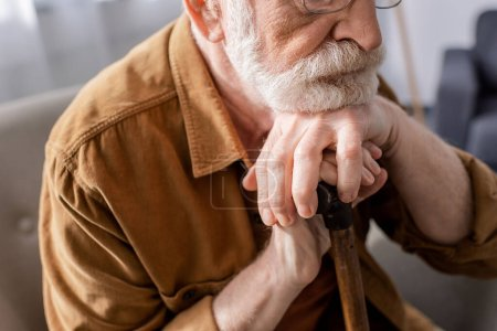 cropped view of depressed senior man sitting and leaning on walking stick