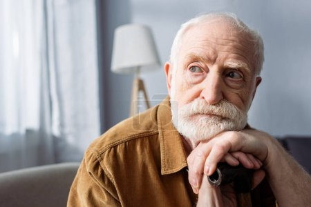 Photo for Senior, lonely man looking away while sitting and leaning on walking stick - Royalty Free Image