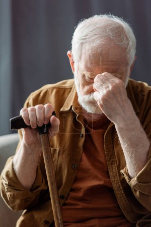 Photo for Senior, lonely man touching face while sitting with walking stick - Royalty Free Image