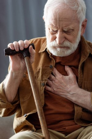 lonely senior man sitting with walking stick and touching chest while feeling bad
