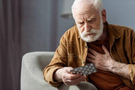 Photo pour Homme âgé se sentant mal, touchant la poitrine et tenant des pilules - image libre de droit